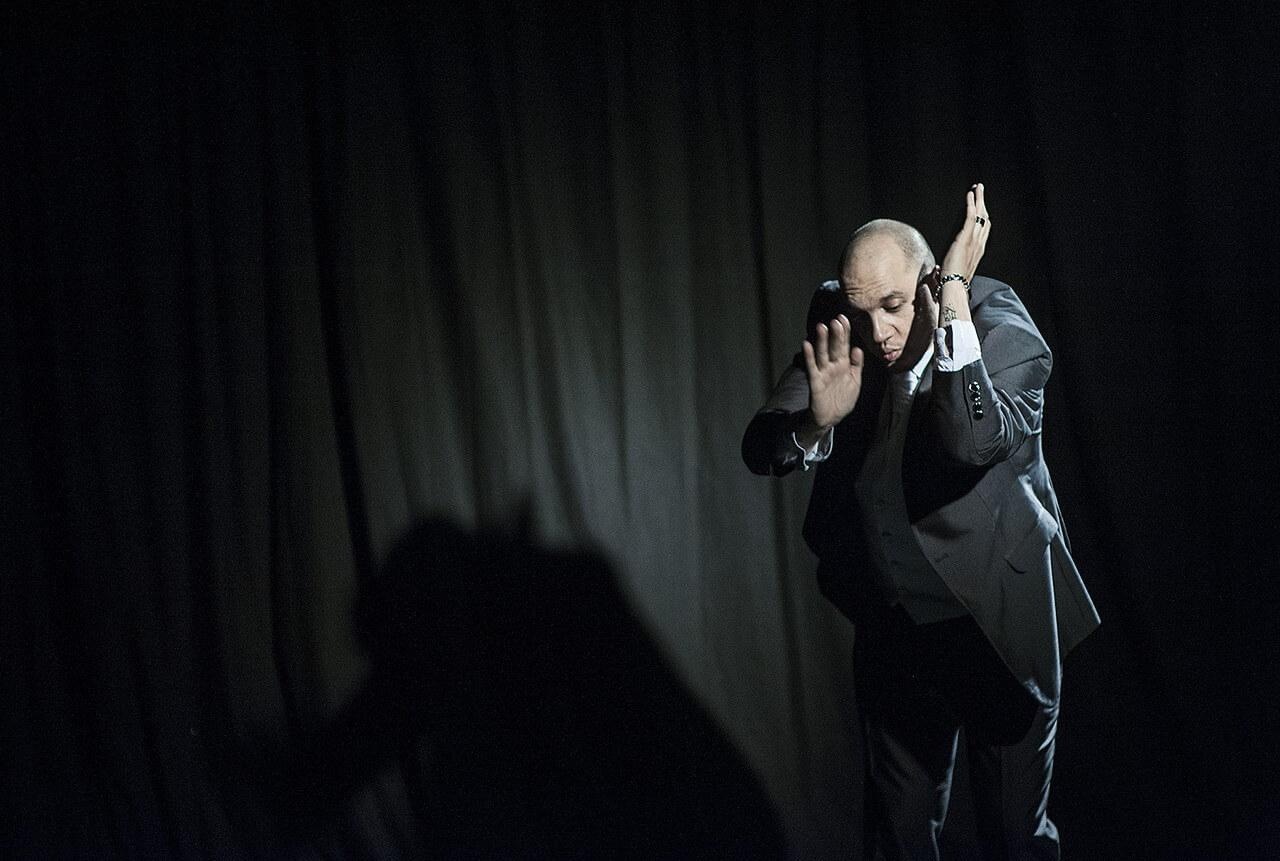 Zdjęcie ze spektaklu Without Music I Am Nothing. Tancerz tańczy z rękami uniesionymi przy twarzy.