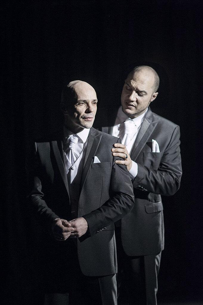 Zdjęcie ze spektaklu Without Music I Am Nothing. dwóch tancerzy w szarych garniturach. jeden stoi za drugim i trzyma ręce na jego ramionach.