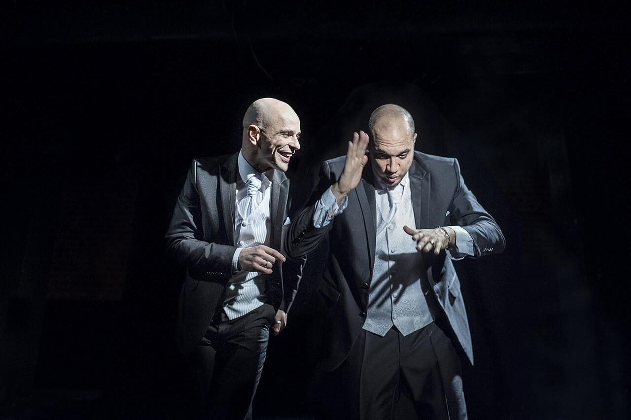 Zdjęcie ze spektaklu Without Music I Am Nothing. dwóch aktorów w szarych garniturach. ten z lewej nachyla się do tego z prawej z uśmiechem. Drugi udaje że gra na bębnie.