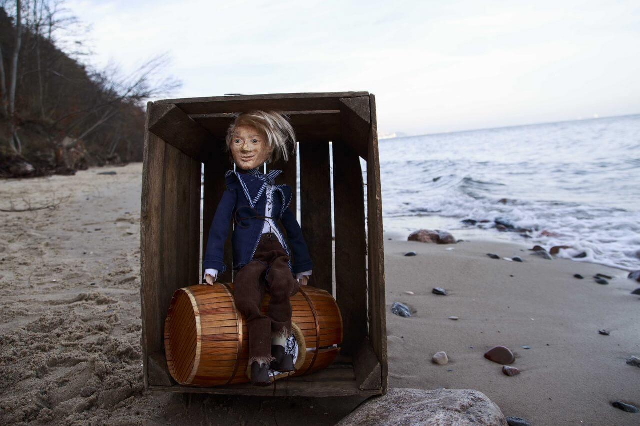Zdjęcie do spektaklu Dzielny Kapitan Ahab. Zdjęcie na plaży. Pokazuje lalkę chłopca o blad włosach siedzącego na beczce w drewnianej skrzyni.