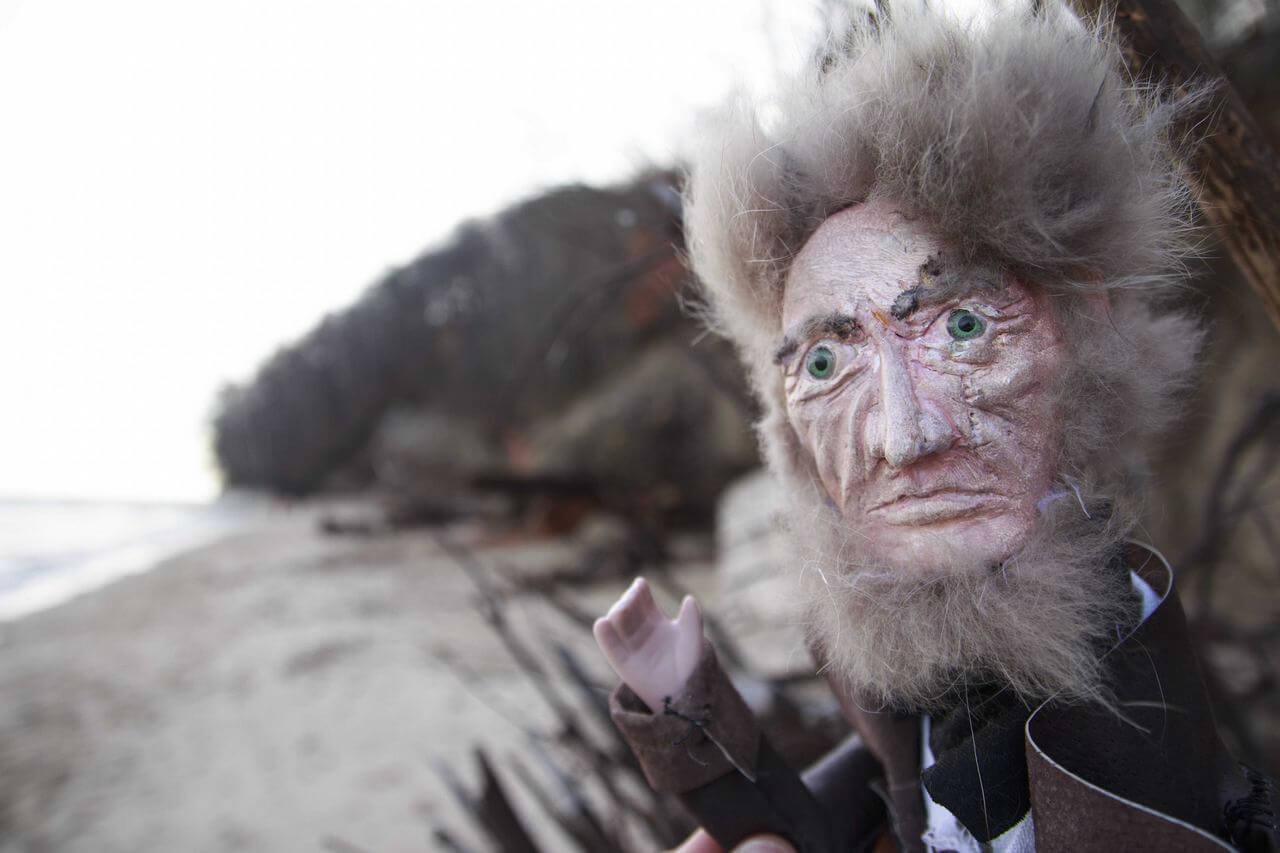 Zdjęcie do spektaklu Dzielny Kapitan Ahab. Zdjęcie na plaży. Pkazuje kapitana o rozczochranych siwych włosach machającego rączką.