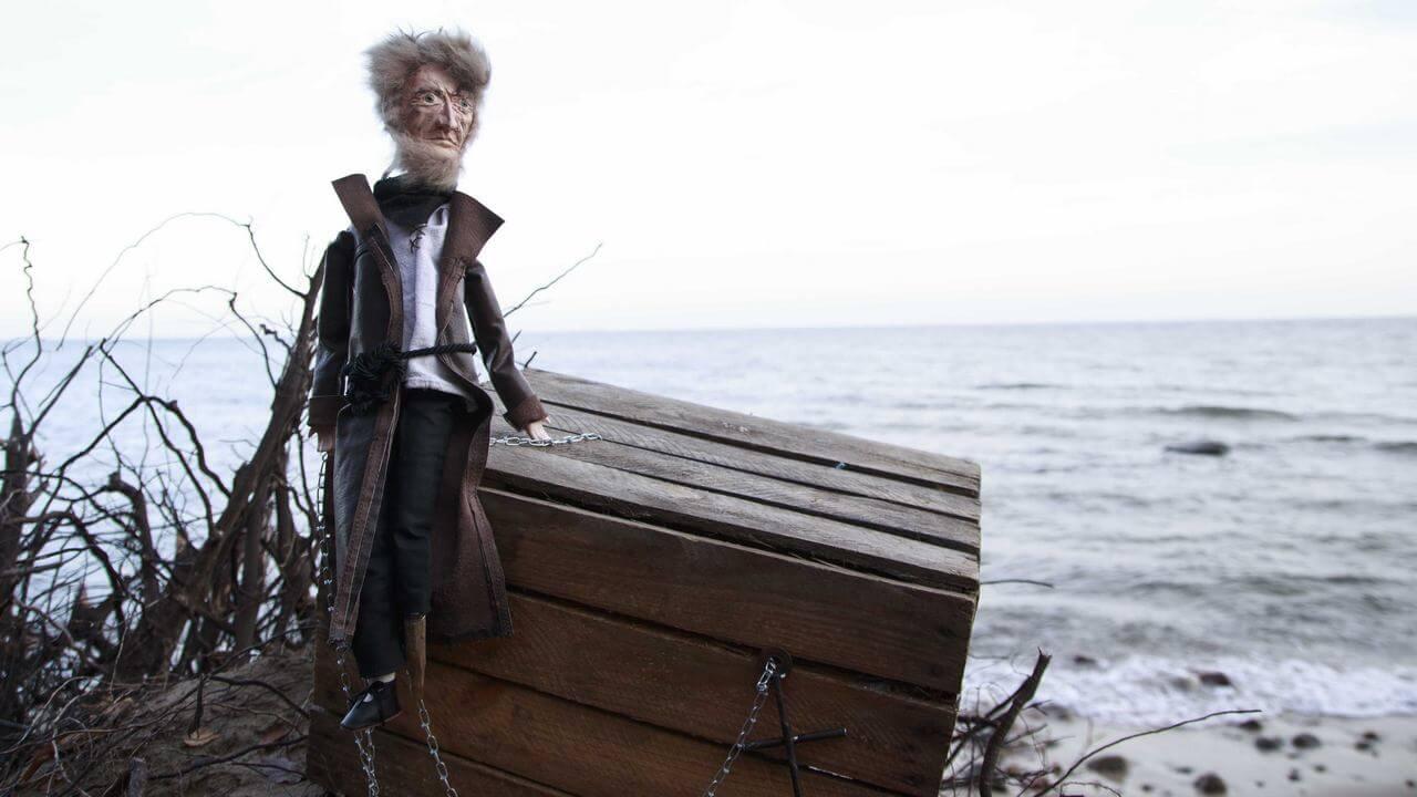 Zdjęcie do spektaklu Dzielny Kapitan Ahab. Zdjęcie na plaży. Pokazuje lalkę kapitana siedzącą na drewnianej skrzyni. w tle morze.