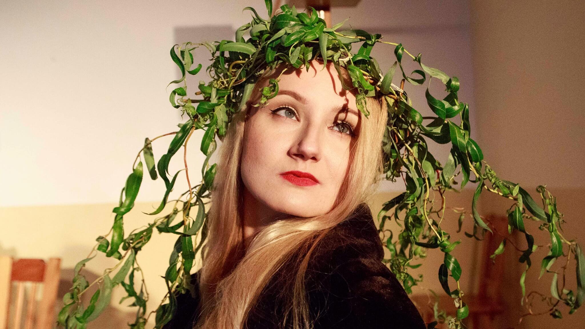 Aktorka o długich bląd włosach i czerwonych ustach z wiankiem z zielonych lisci na głowie.
