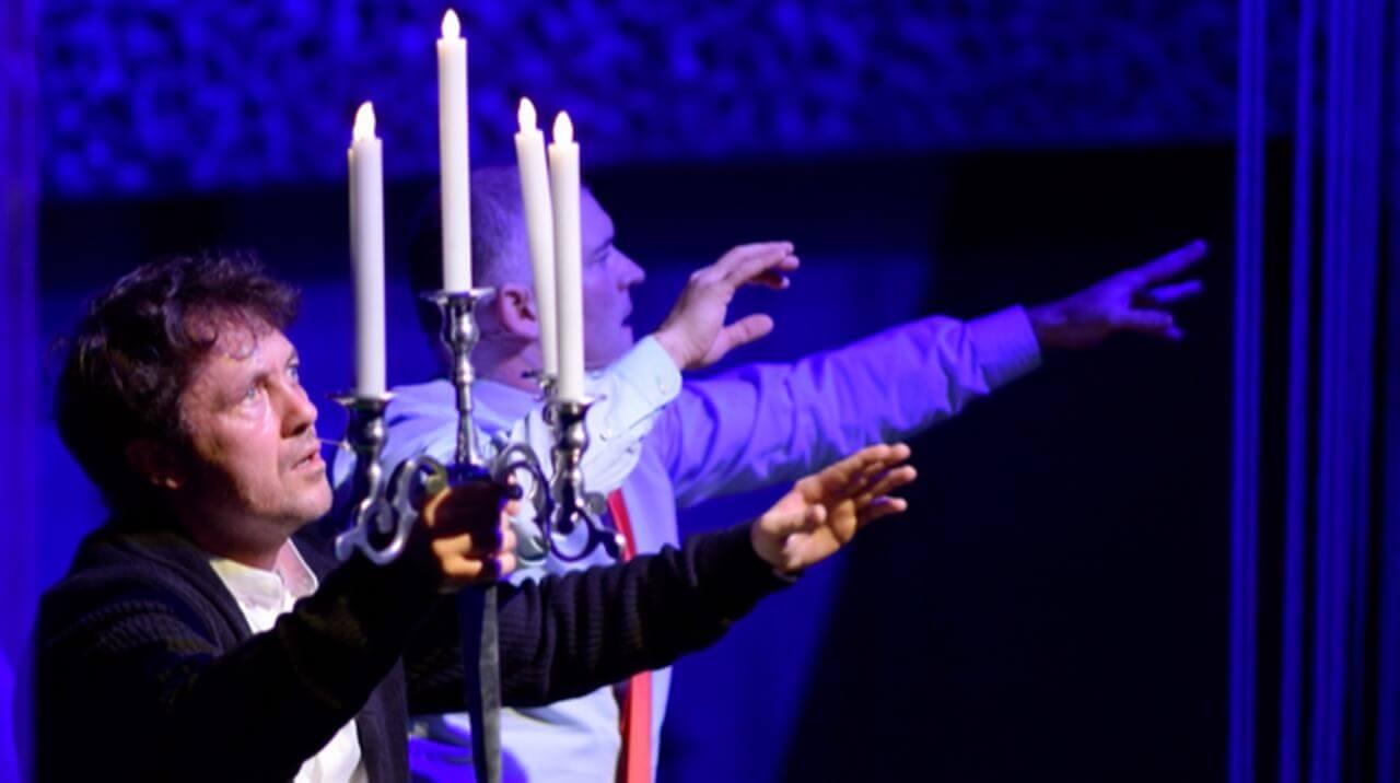 Zdjęcie do spektaklu Dobroć nasza dobroć. Dwóch mężczyzn z wyciagnietymi przed siebie rękoma. jeden trzyma świecznik z piecioma świecami.