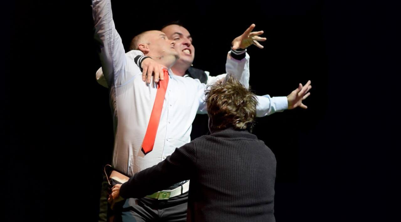 Zdjęcie do spektaklu Dobroć nasza dobroć. Trzech mężczyzn jeden posrodku z uniesonymi rekami, drugi trzyma mu ręce na ramionach a trzeci obejmuje go w pasie.