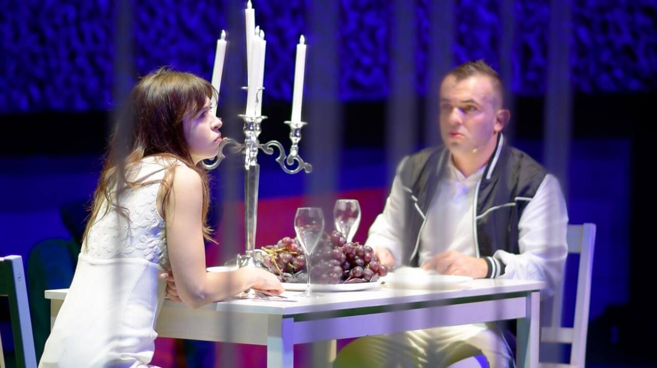 Zdjęcie do spektaklu Dobroć nasza dobroć. Kobieta i mężczyzna siedzą przy stole. Na środku lezą winogrona i stoi świecznik.