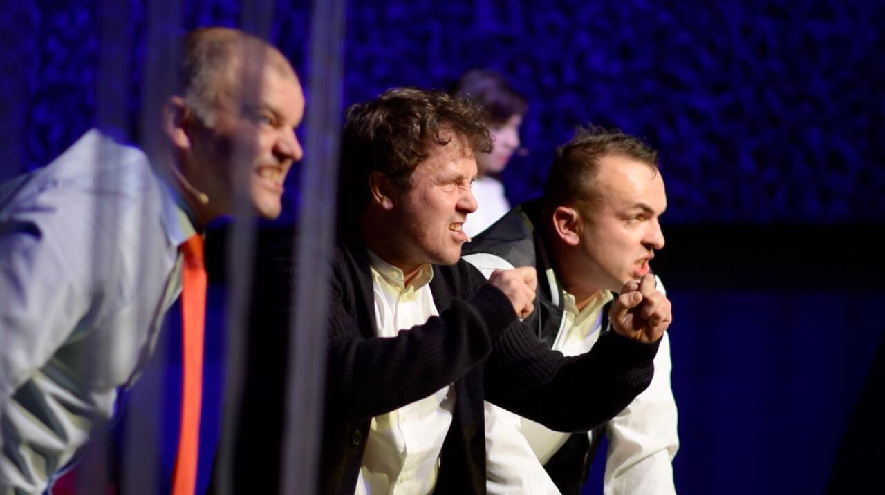 Zdjęcie do spektaklu Dobroć nasza dobroć. trzech mężcyzn w bojowej postawie. Szczerzą zęby do widzów.