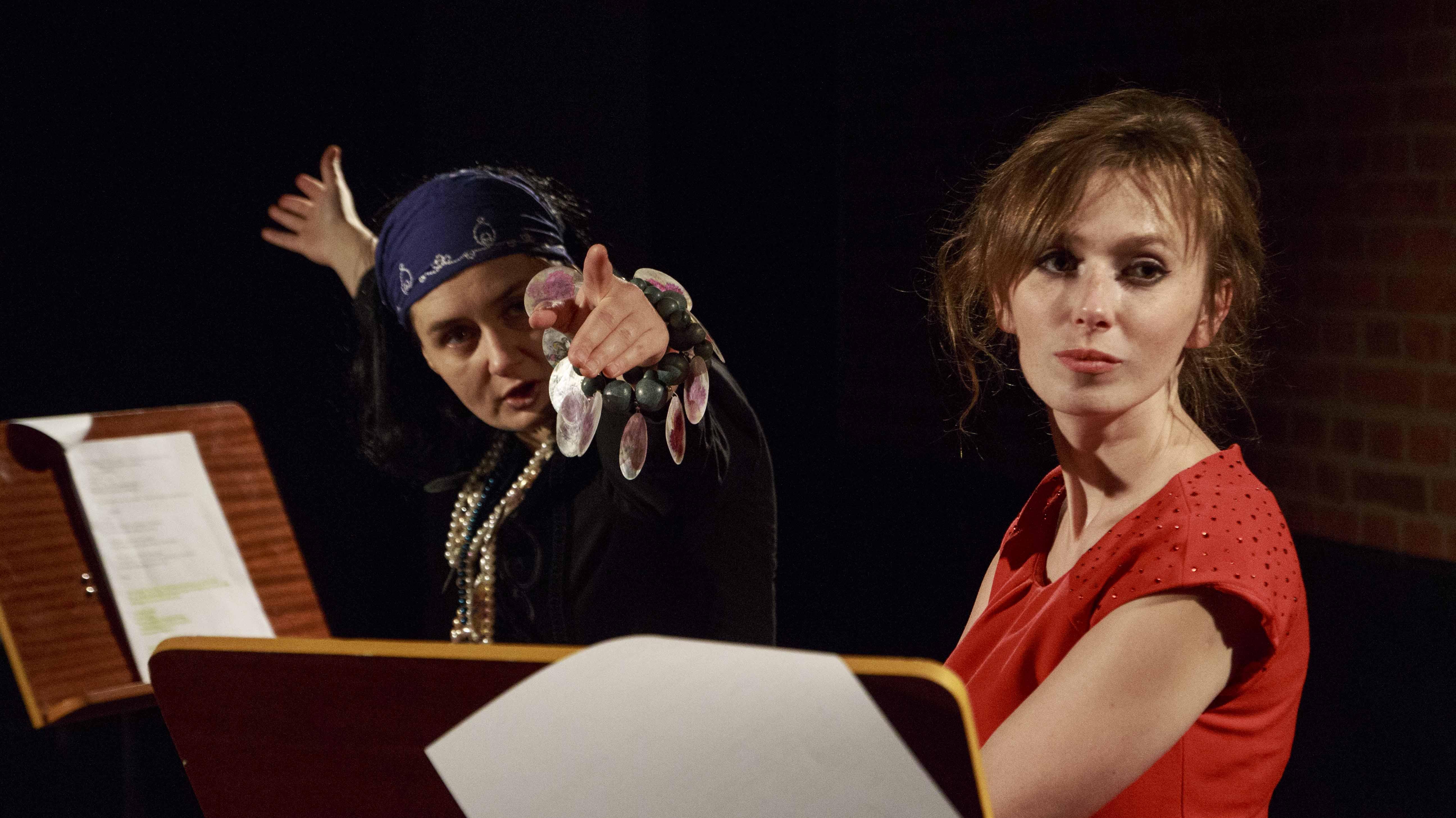 Zdjęcie ze spektaklu Dzielnice cudów. Dwie aktorki przy pulpitach z tekstem. Na pierwszym planie aktorka w czerwonej sukience, na drugim aktorka przebrana jak cyganka.