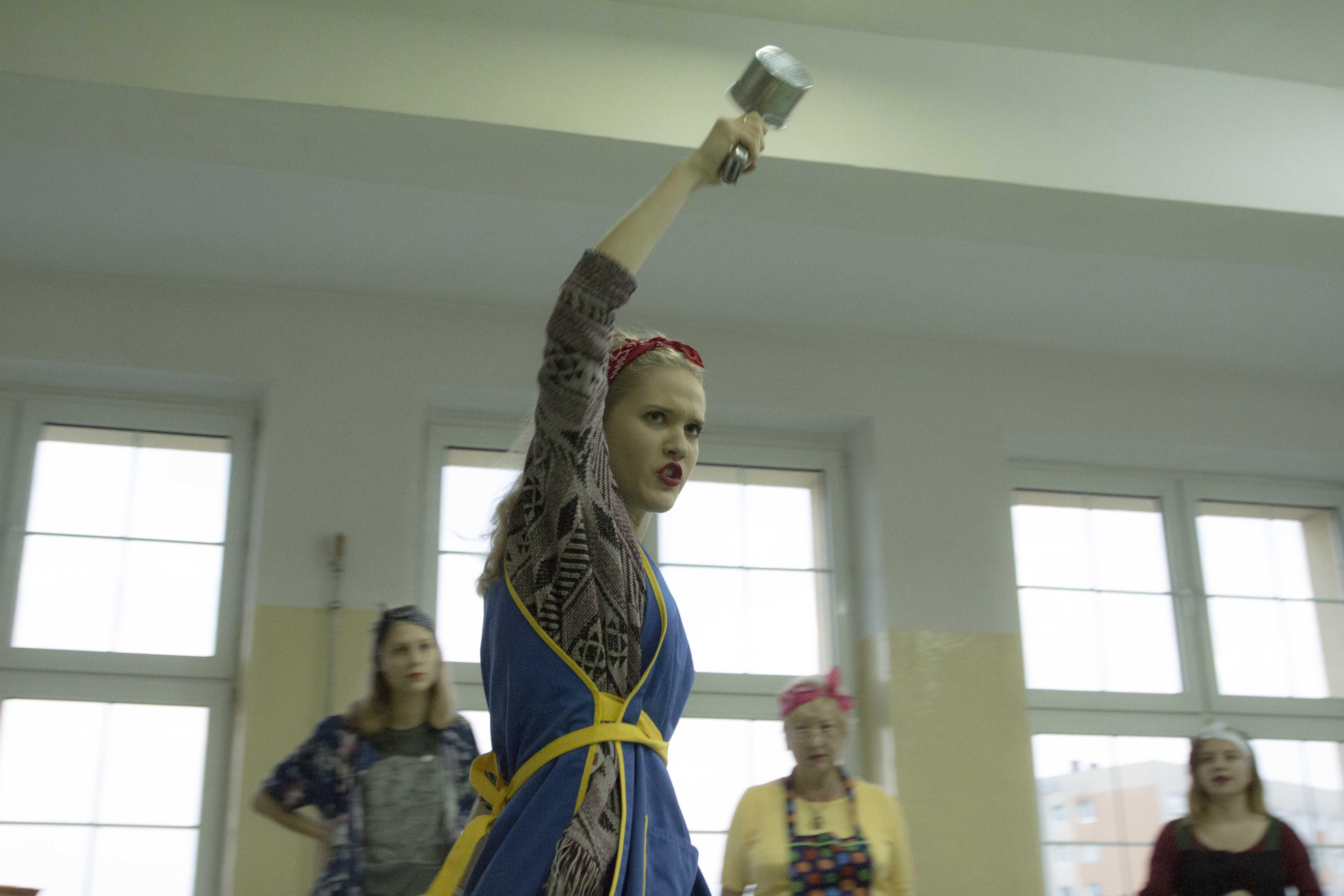 zdjęcie z projektu Dzwięczące wieżowce. Aktorka z niebieskim fatuchu z uniesiona wysoko ręką z jakimś urządzeniem kuchennym