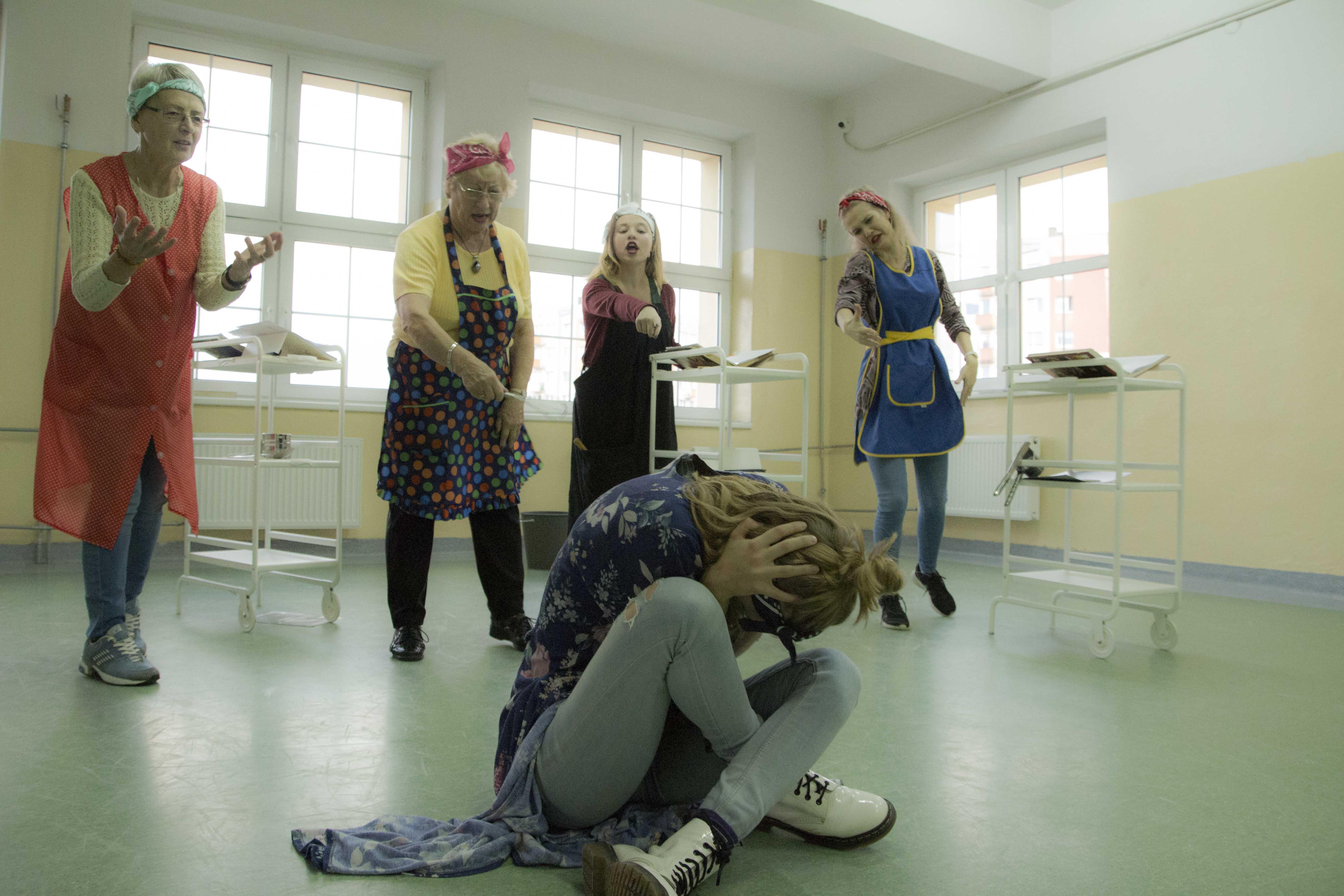 zdjęcie z projektu Dzwięczące wieżowce. Pięc aktorek w kuchennych fartuchach. na pierwszym planie jedna siedzi po turecku z głową ukryta w dłoniach. Cztery pozostałe stoja nad nia wskazując na nią palcami.