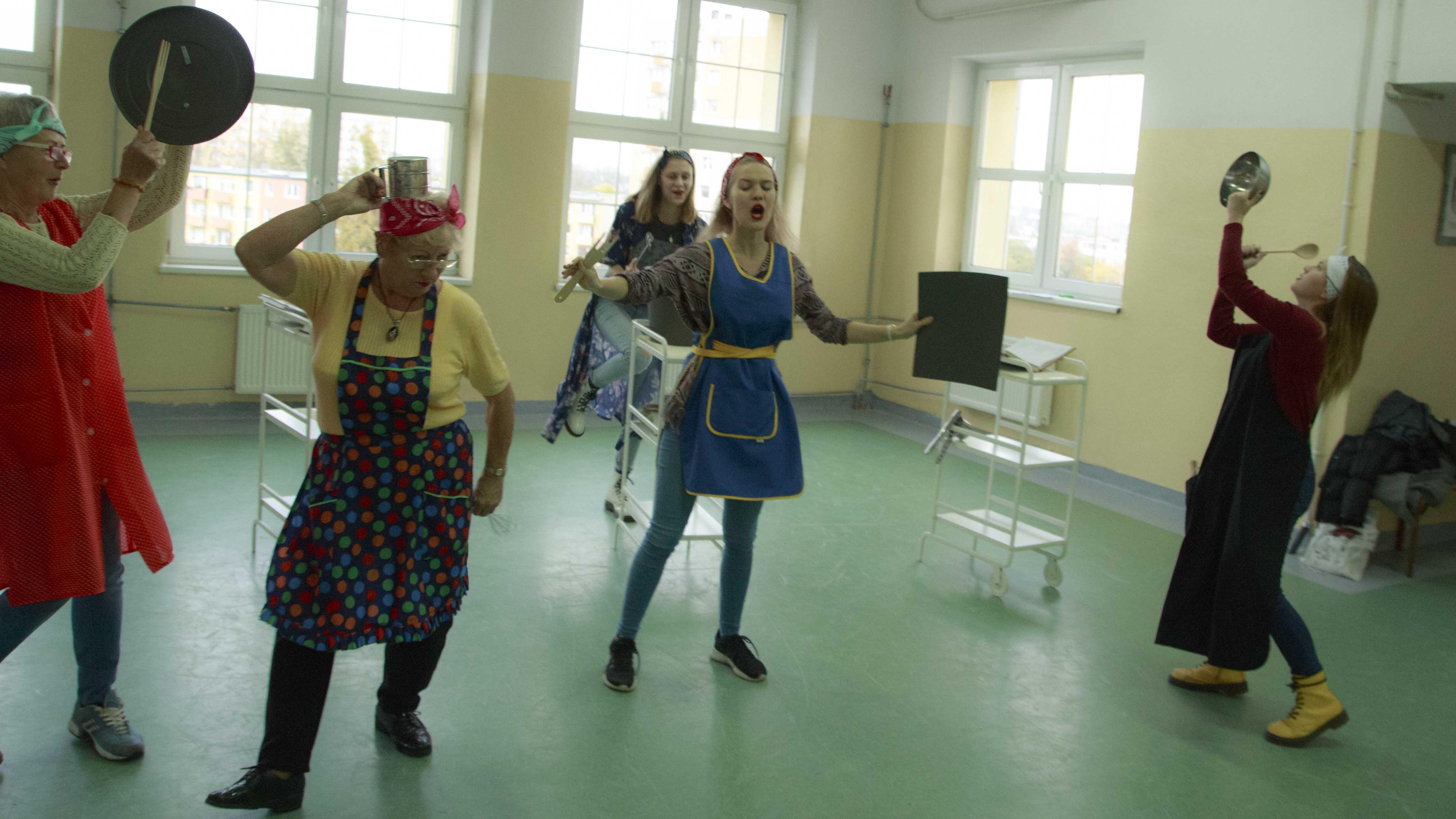 zdjęcie z projektu Dzwięczące wieżowce. Pięć aktorek w fartuchach kuchennych chodzi po sali i śpiewa.