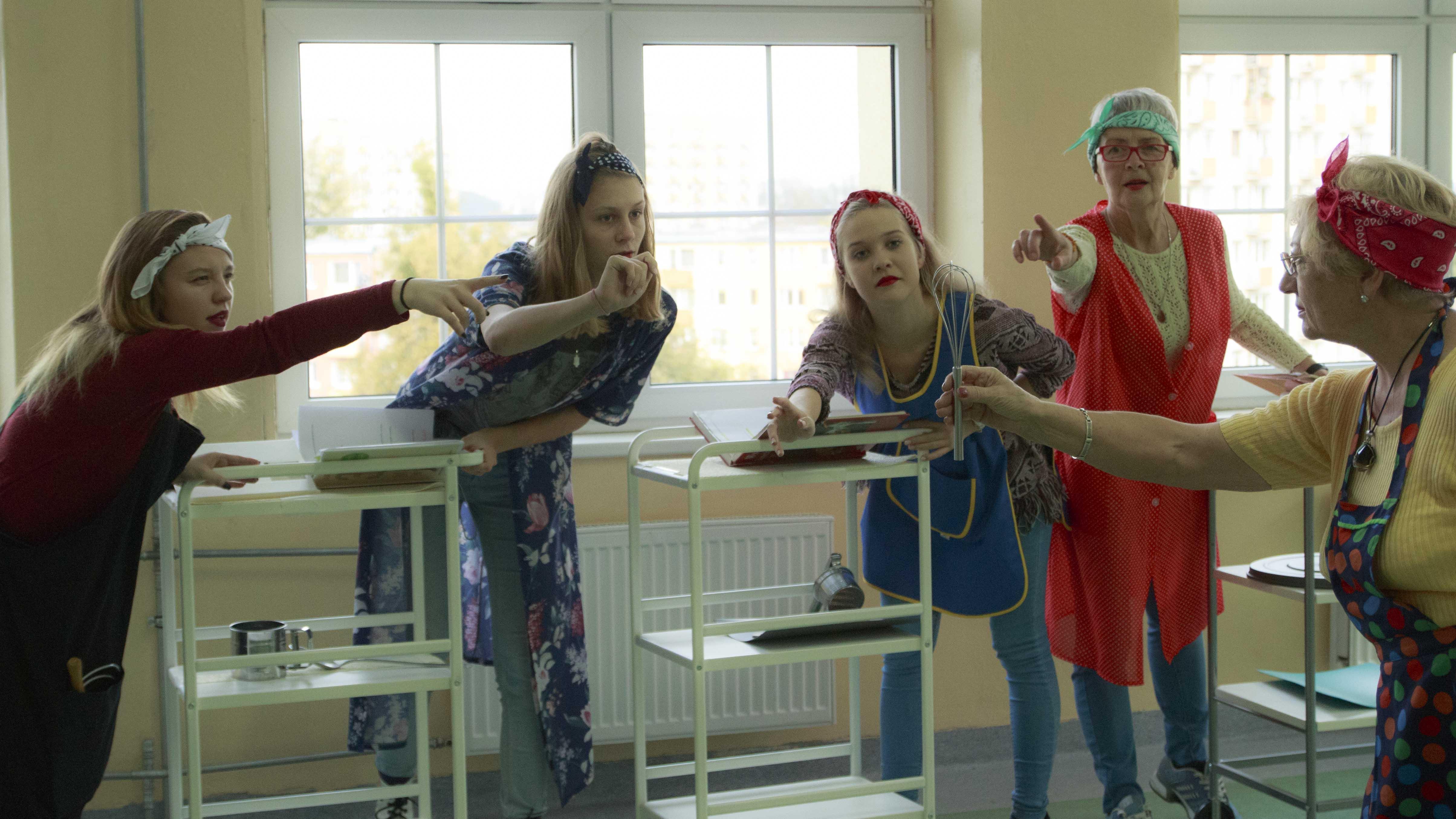 zdjęcie z projektu Dzwięczące wieżowce. Pięć aktorek w fartuchach kuchennych pochyla się i wskazuje palcami na mieszadło trzymane prze jedną z nich.