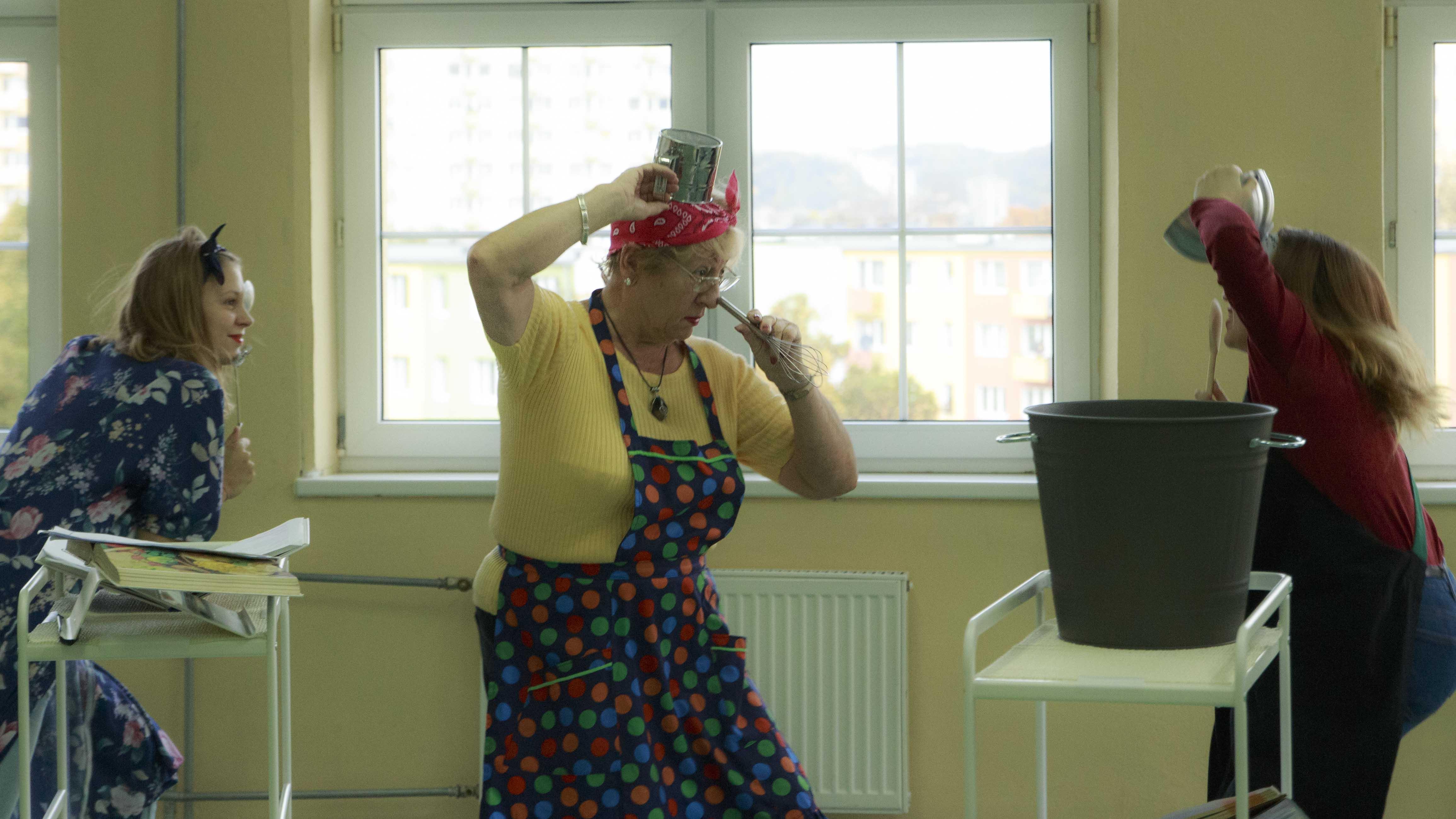 zdjęcie z projektu Dzwięczące wieżowce. Aktorka w fartuchu kuchennym z kubkiem na głowie i mieszadłem przyłozonym do nosa.