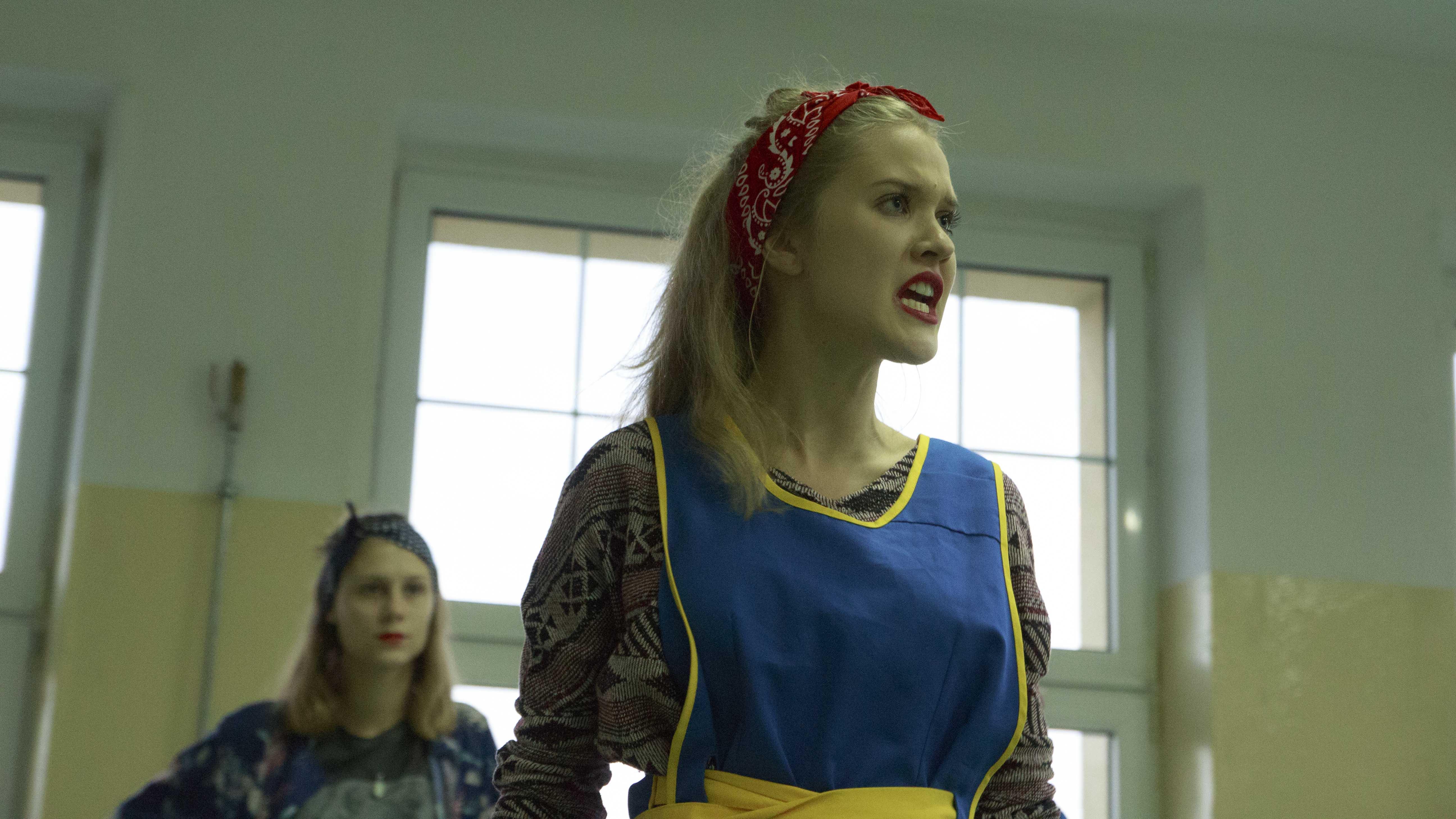 zdjęcie z projektu Dźwięczące wieżowce. Aktorka w niebieskim fartuchu i z czerwoną bandamką na głowie.