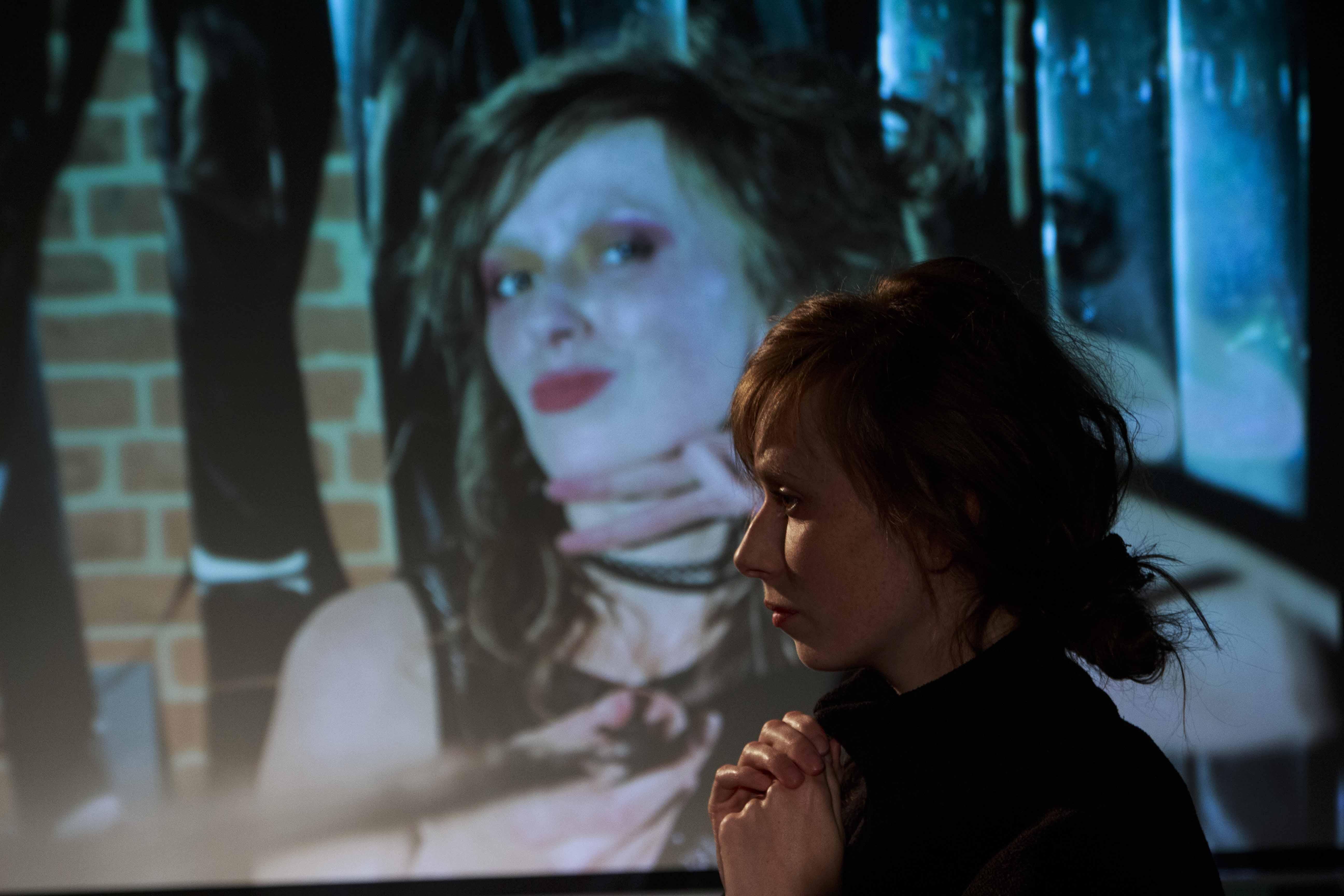 Zdjęcie z Teatru Forum. Aktorka z rekami splecionymi pod brodą stoi na tle wyświetlonego swojego zdjęcia w bardzo odwaznej pozie.