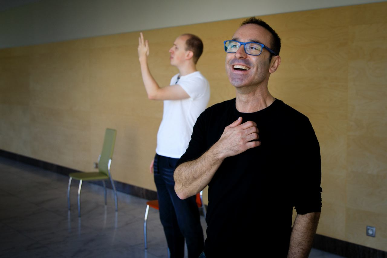 Zdjęcie do spektaklu Role. dwóch aktorów. Na pierwszym planie aktor w czarnej bluzie, usmiechniety w niebieskich okularach. Na drugim planie aktor w białek koszulce z uniesioną do góry reką.