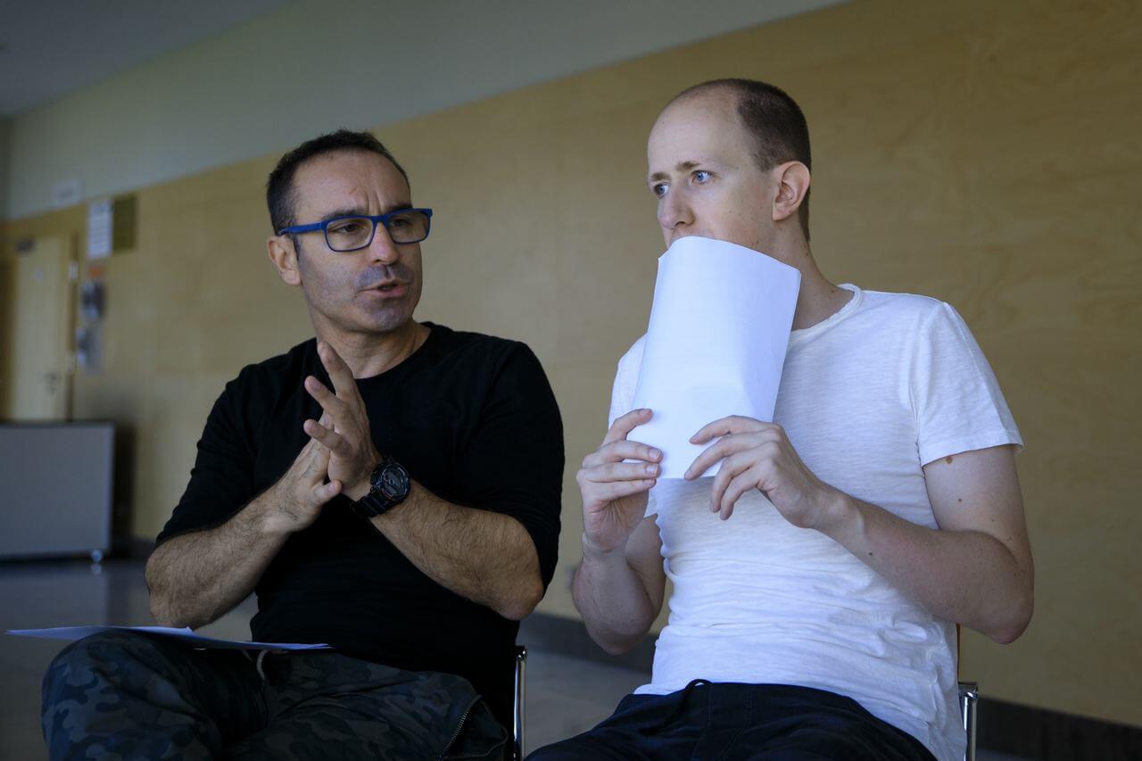 Zdjęcie do spektaklu Role. Dwóch aktorów. N apierwszym planie aktor w białej koszulce zakrywa usta kartka papieru. Obok drugi aktor ubrany na czarno ze złozonymi przed soba rekami.